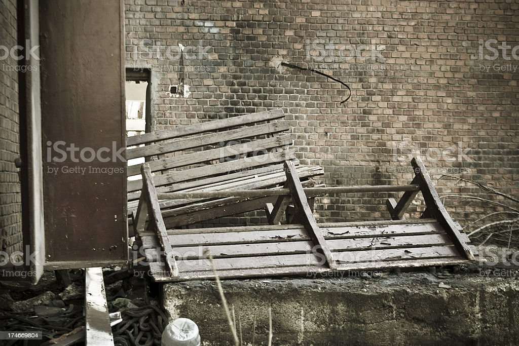 Destroyed wooden bench in front of a groungy brick wall royalty-free stock photo