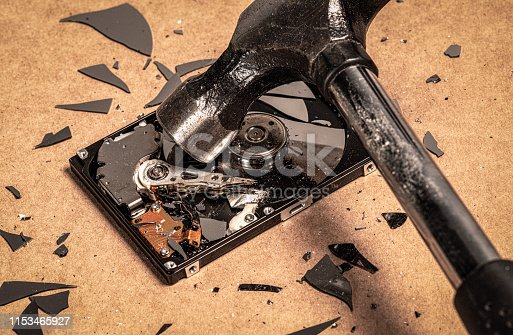 Close-up showing a hammer being used to smash the disks of a hard drive.