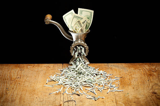 destroying dollars with a grinder - money black background stock photos and pictures