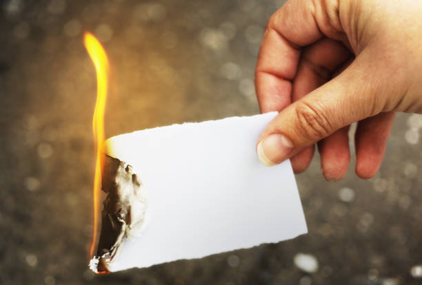 destroying the evidence: female hand burning paper - burning stock pictures, royalty-free photos & images