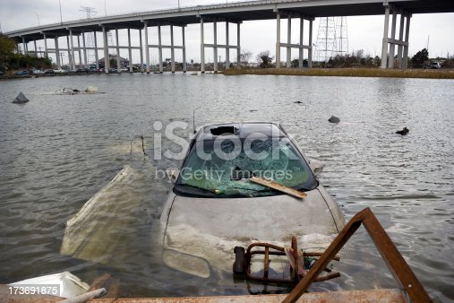 A flooded car sits hopelessly submerged near an overpass.