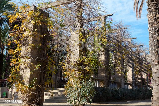 Detail and arcade of Joan Miro park in Barcelona in winter sunshine and season. A senior man is sitting between stony columns.