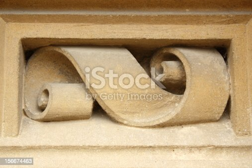 ribbon shaped detail carved in stone on facade of old house