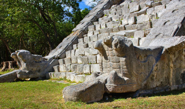 Detail for the serpent's head at the base of the stair, with its body and tail going to the top. Nobody. Chichen Itza, mayan pyramid: Yucatan, Mexico - Mar 2, 2018 stock photo
