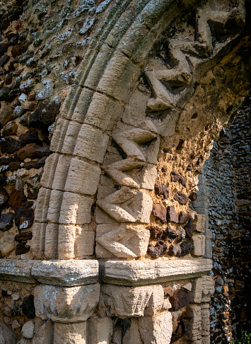 Detail from part of a Norman arch in the ruins of the Romanesque-style St James' church at Bawsey in Norfolk, Eastern England. The church was built of the local ginger-coloured carrstone, with some flint and limestone, on a slight hill during the 11th or 12th centuries, with parts replaced or enlarged in the 14th or 15th centuries. It fell into disuse in the 18th century. Bawsey is a sparsely populated village near King's Lynn which was once closer to The Wash than it is now, the coastline having moved over the centuries.