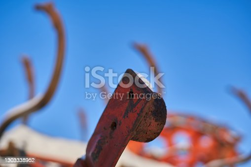 Detail from a red agricultural machine, harrow, plow. In winter with snow on it against a blue sky. Close up, selective focus.