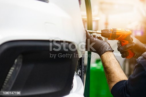 498888104 istock photo Detail image of mechanic hands with tool, changing tyre of car, with blurred background of garage. 1080147196