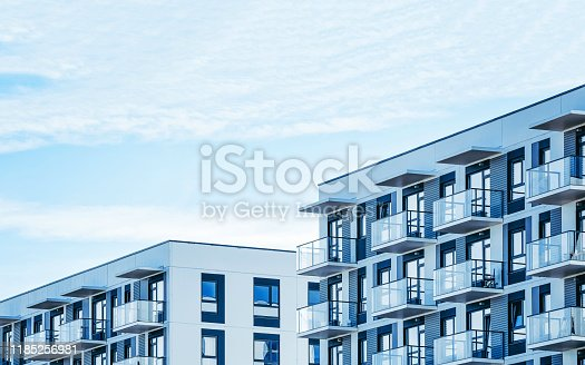 Detail in Modern residential apartment flat building exterior. Fragment of New luxury house and home complex. Part of City Real estate property and condo architecture. Copy space. Blue sky