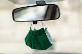close up green face mouth nose mask hanging under rear-view mirror of car at front wind shield screen in times of covid-19 coronavirus