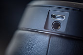 Detail of a 3.5 jack and usb port on a black headset with leather cups with shallow depth of field