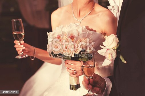 istock Detail of a bride and groom holding glasses of wine 498829209