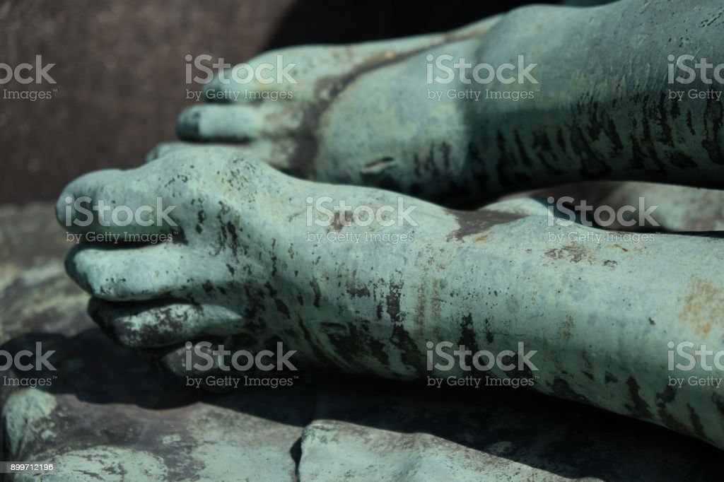 Detail of a bronze statue of the dead Christ, marks from the nails in his feet. Medieval sculpture of a dead Jesus after the crucifixion in a local churchyard in Prague. Close up of feet. stock photo