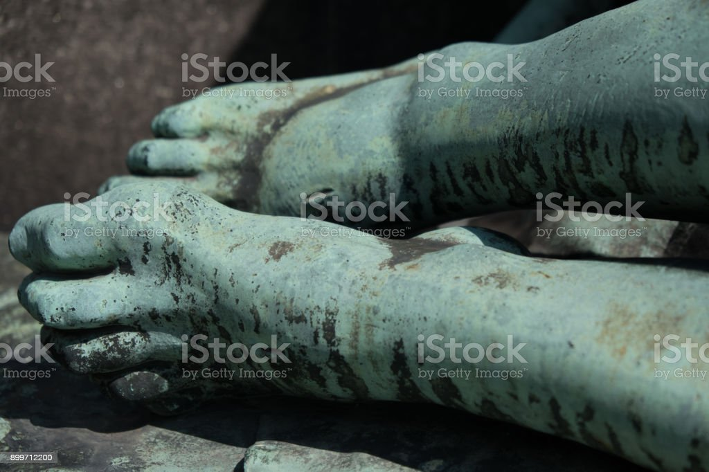 Detail of a bronze statue of the dead Christ, marks from the nails in his feet. Medieval sculpture of a dead Jesus after the crucifixion in a local churchyard in Prague. stock photo