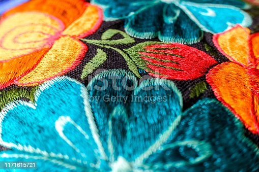 Detail of a colorful embroidery with flower motifs in brightly colored fabrics.