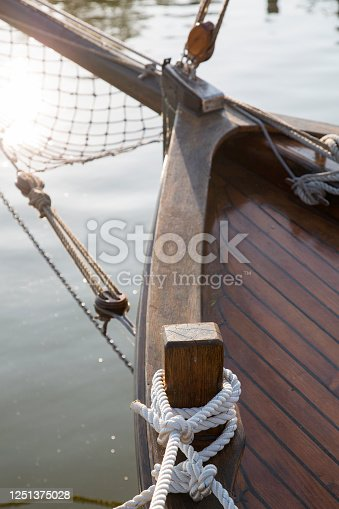 Detail of a deck of a wooden sailboat tied with a rope