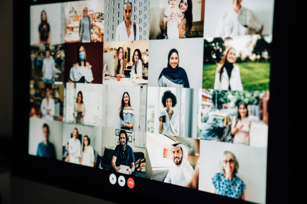 Detail of a desktop PC with many people having a meeting at distance stock photo