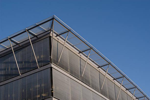 détail d'un bâtiment futuriste avec écran solaire en métal couvrant les fenêtres. - cosmetique store photos et images de collection