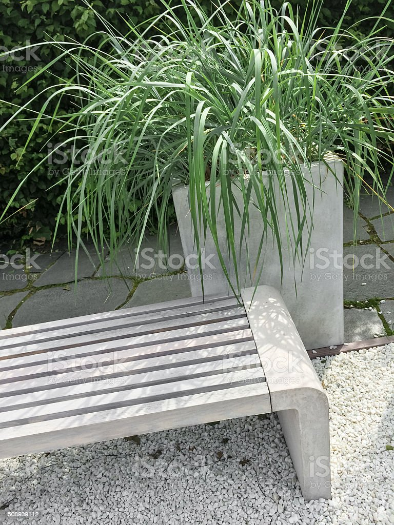 Detail of a garden with decorative grass and bench stock photo