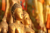 Detail of a golden Buddha face inside a temple in the golden triangle of South East Asia, comprising the countries of Thailand, Myanmar, Laos and Cambodia. More buddhist sculpture are visible in the background. Religion and spirituality of asian culture.