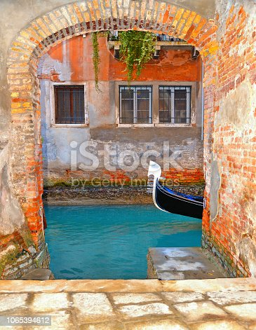 Detail of a gondola floating on the waterseen from an internal courtyard with facade of old building with windows in background. Venice Italy