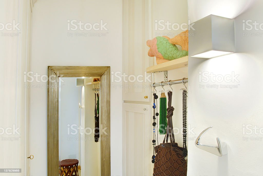 Detail of a house's corner: mirror, coat hooks, wall cabinets stock photo