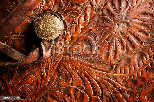 A detail of a horse saddle tooled with a filigree design reminiscent of the old west in American culture.