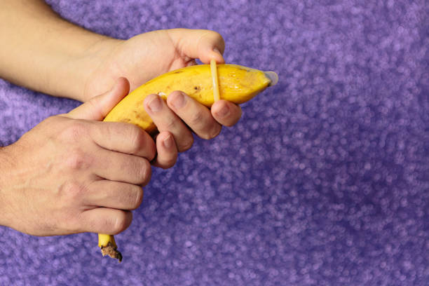 Detail of a man's hand correctly placing a condom on a banana.