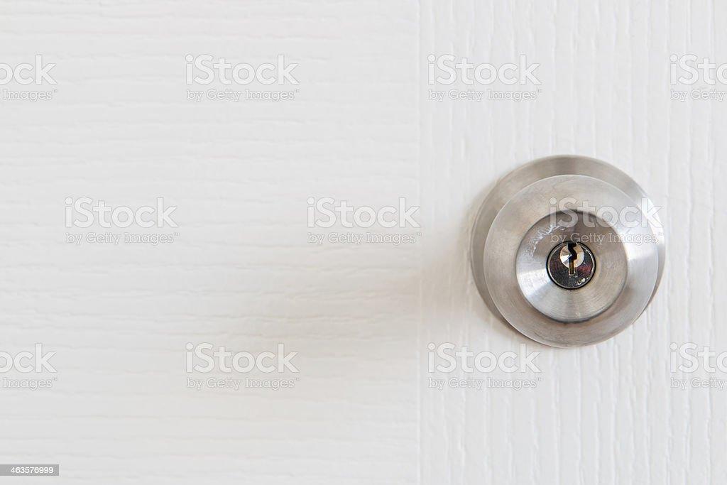Detail of a metallic knob on white door stock photo
