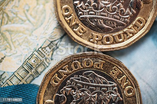 Detail of a One Pound (GBP) coin. The Big Ben design in the background comes from a 5 GBP banknote.