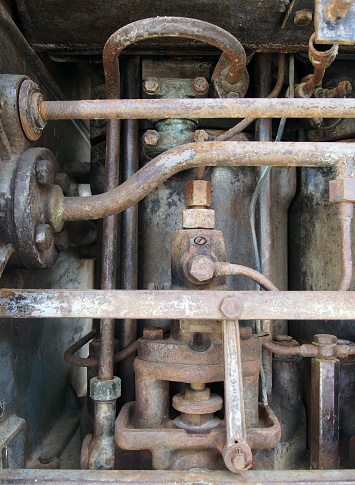 close up of a large old abandoned marine diesel engine showing rusting pipes and cylinders and bolts