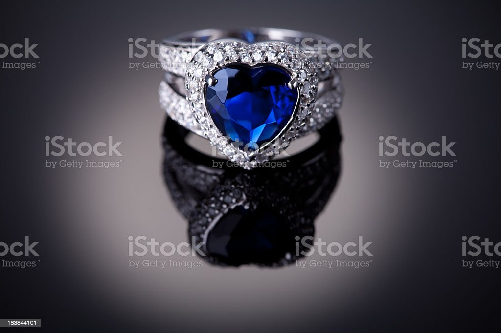 Detail of a silver ring with a blue heart-shaped gem center stock photo