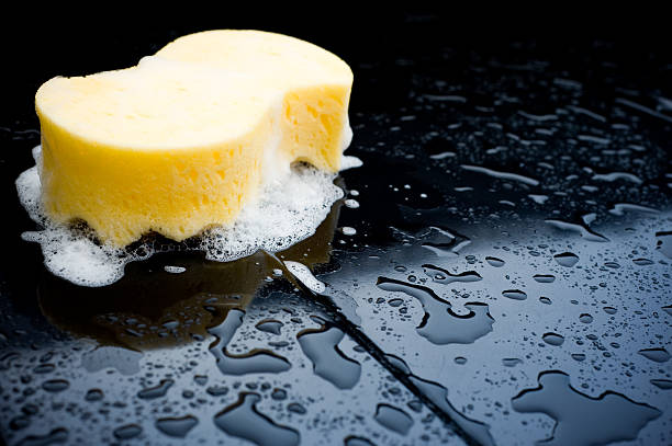 Detail of a sponge over a black car during a car wash stock photo