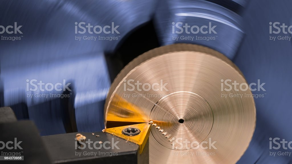 Artistic industrial background. Bronze product clamped in blue...
