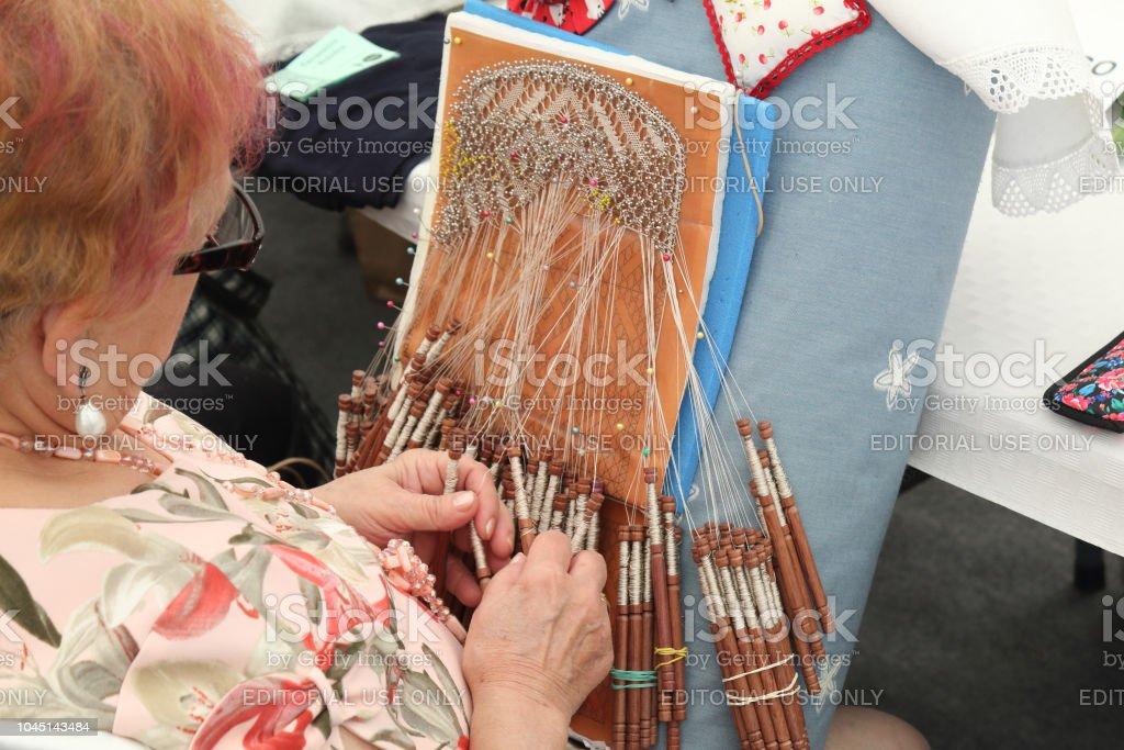 Un detalle de una mujer de un bordado con pasadores y filamento blanco de costura enrollada en carretes en una feria tradicional en el pueblo español aragonés rural Ainsa - foto de stock