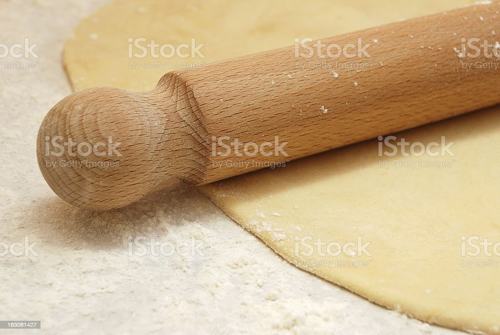Detail of a wooden rolling pin on rolled out pastry royalty-free stock photo