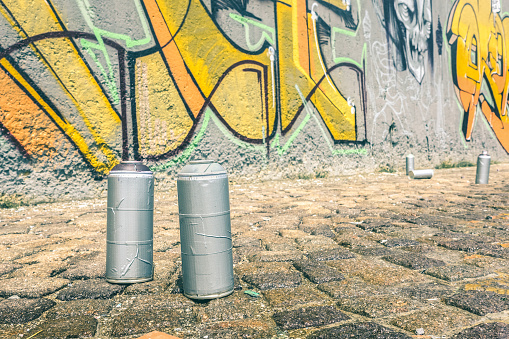Detail of aerosol spray can at colorful graffiti on wall - Modern street art concept with urban painting perform and murales live preparation - Bright vintage retro filter