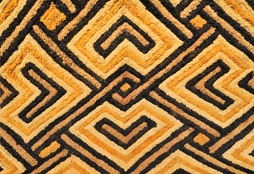 Detail of a Kasai velvet tapestry, hand-woven by the Kuba tribe people of the Kasai district of the Democratic Republic of Congo (Zaire).These tapestries with geometric designs and earth tones are woven in raised relief and made of palm leaf fibers or raffia.