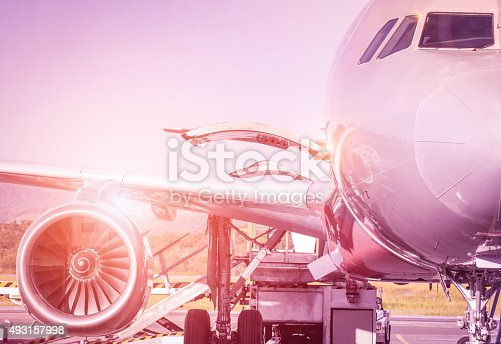 Detail of airplane at terminal gate before takeoff - Travel concept and wander around the world in international airport at sunset - Vintage marsala filtered look with sunshine halo