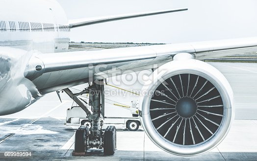 istock Detail of airplane engine wing at terminal gate before takeoff - Wanderlust travel concept around the world with air plane at international airport - Retro contrast filter with light blue color tones 669989594