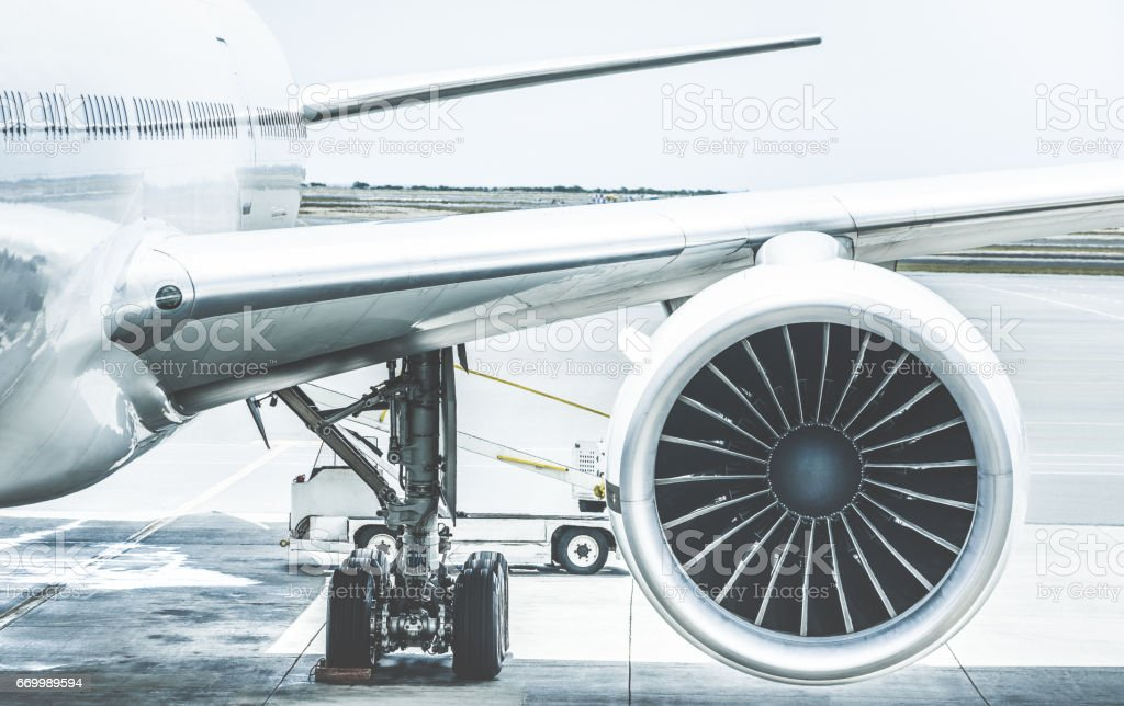 Detail of airplane engine wing at terminal gate before takeoff - Wanderlust travel concept around the world with air plane at international airport - Retro contrast filter with light blue color tones stock photo