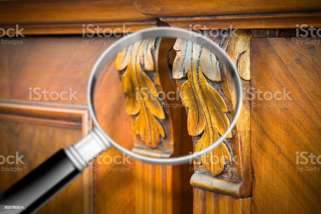Detail of an antique wooden italian furniture just restored with a magnifying glass on foreground looking for woodworm threat detection stock photo