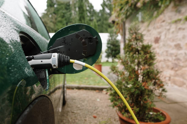 Detail of an electric car plugged in stock photo
