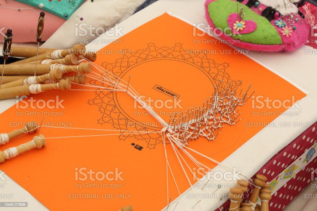 Un detalle de un bordado siendo cosido con alfileres y filamento blanco enrollado en carretes en una feria tradicional en el pueblo español aragonés rural Ainsa - foto de stock