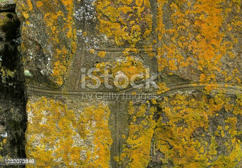 detail of an old stone wall, discolored by moss and lichens, which surrounds an old cemetery in Orient, NY, on the North Fork of Long Island