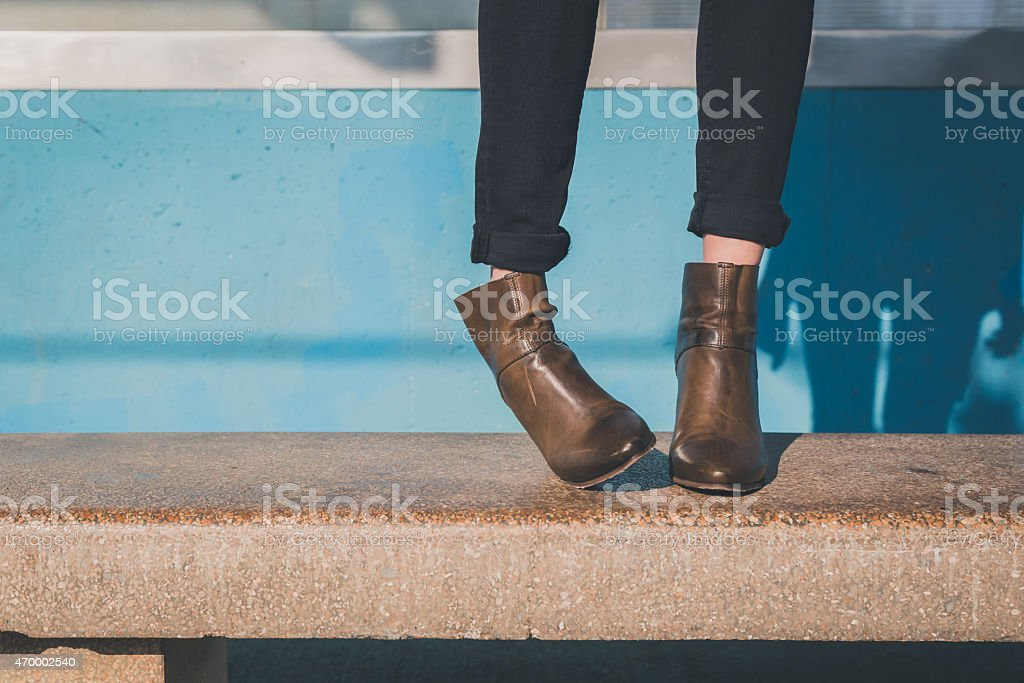 Detail of ankle boots in a metro station stock photo