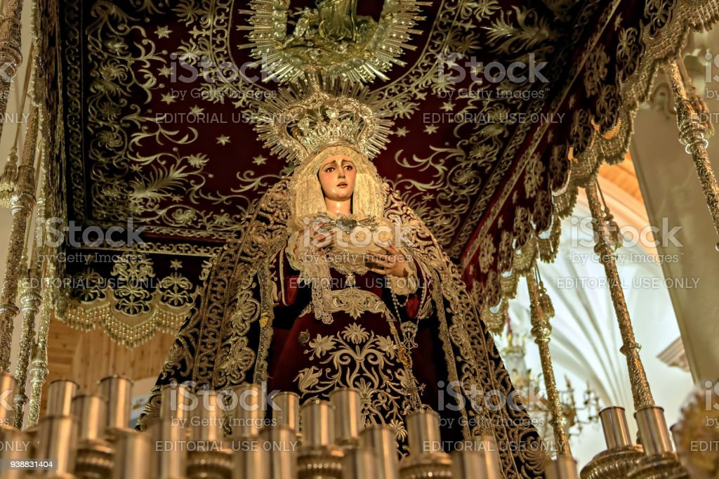 Detail of antique religious float carrying a wooden sculpture depicting Virgin Mary during Holy Week Easter parade in Huelva. stock photo