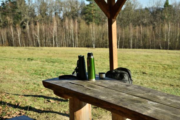 Detail of basic aids for a hiker in nature thermos for tea and binoculars stock photo