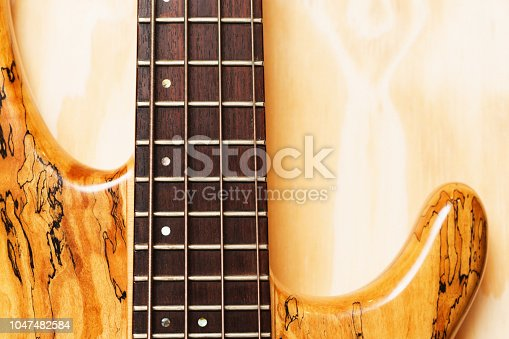 Detail of neck and part body of a bass guitar made from spalted maple.