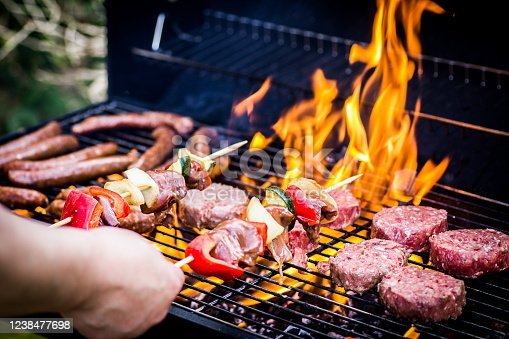 istock Detail Of Beef Burgers and sausages Cooking On A Barbecue 1238477698
