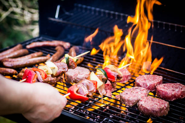 detalle de hamburguesas de ternera y salchichas cocinando en una barbacoa - grilling fotografías e imágenes de stock